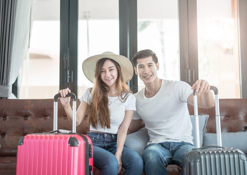Espera de assento dos pares asiáticos novos elegantes com bagagem férias e conceito do viajante imagem de stock royalty free