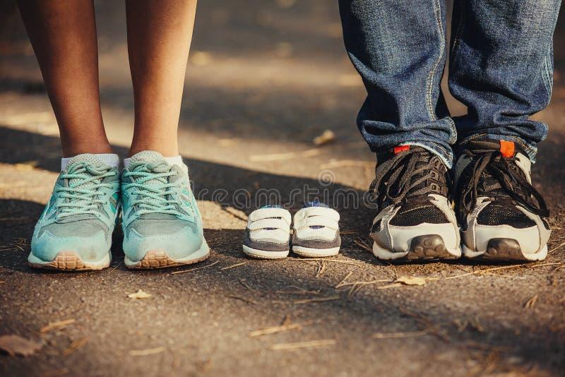 Espera do bebê Montantes pequenos, sapatilhas perto dos pés de meu pai e mãe Mulher gravida, gravidez, maternidade fotos de stock