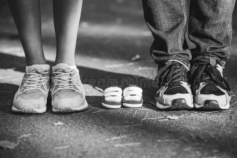 Espera do bebê Montantes pequenos, sapatilhas perto dos pés de meu pai e mãe Mulher gravida, gravidez, maternidade imagem de stock royalty free