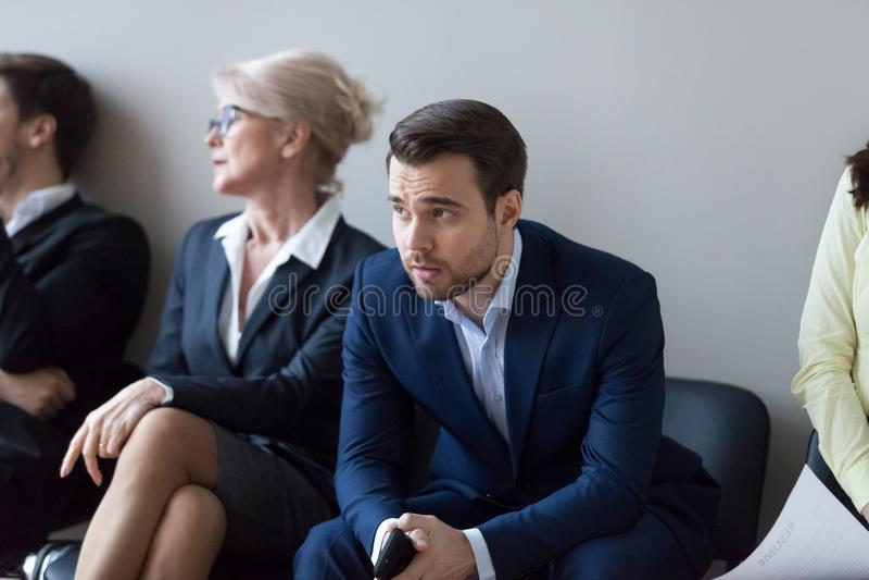 Espera masculina milenar nervosa do empregado na fila para a entrevista imagem de stock royalty free