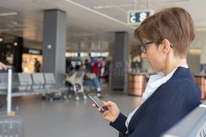 Espera no terminal de aeroporto usando o telefone fotos de stock