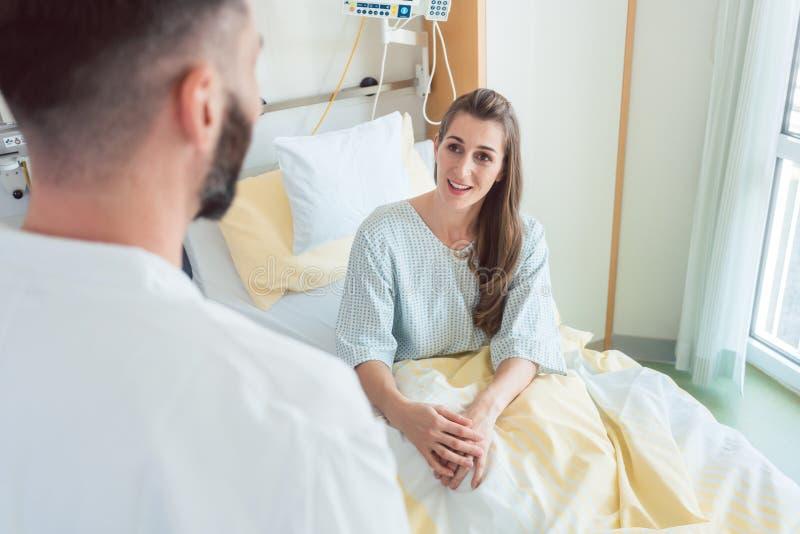 Espera paciente na cama de hospital pelo doutor para vê-la imagens de stock