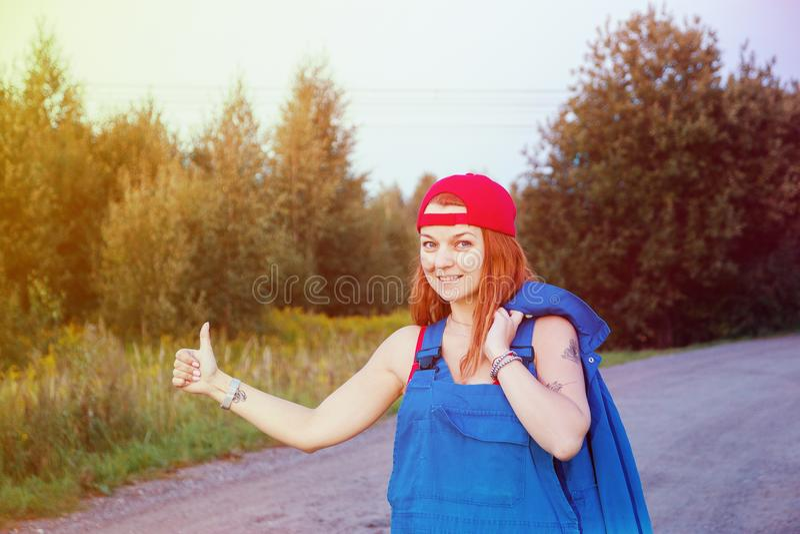 Espera para la ayuda del borde de la carretera Retrato de una mujer joven que se coloca en el camino que intenta parar el coche q fotos de archivo libres de regalías