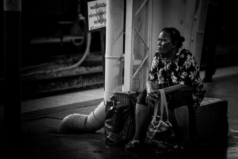 Espera tailandesa de la mujer por hora de salida en la estación terminal del tren principal en Bangkok imagen de archivo