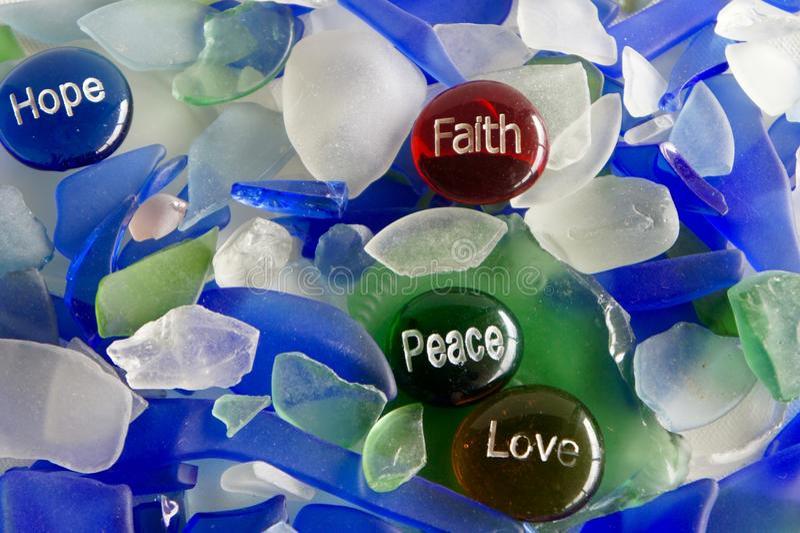 Esperança, fé, paz e amor nas pedras de vidro com vidro do mar fotografia de stock