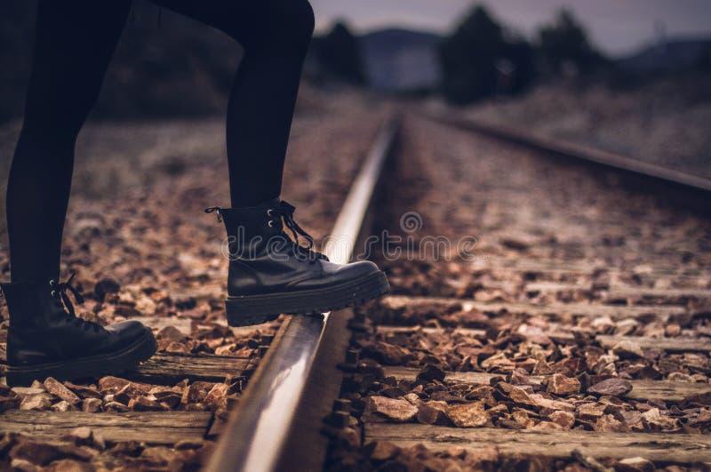 Esperando el tren en todo el mundo con las botas grandes fotos de archivo
