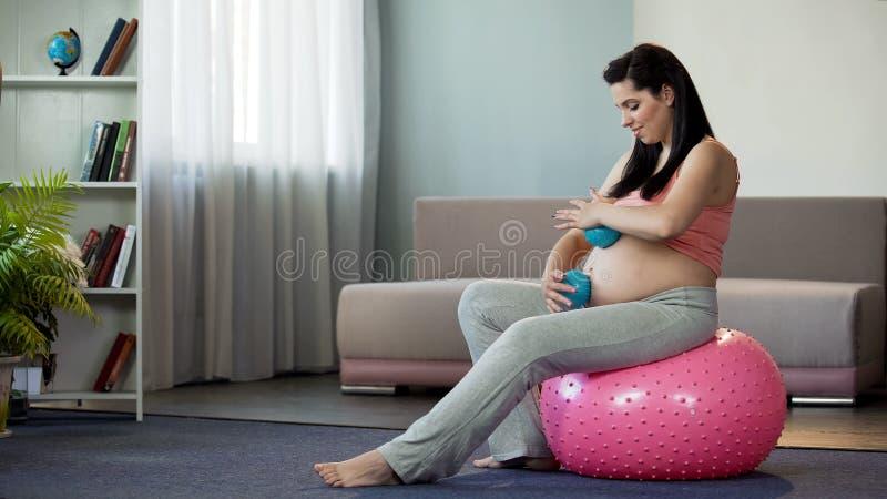 Esperando a mulher que faz massagens a barriga grávida, tomando da aptidão do bebê e do corpo imagem de stock royalty free