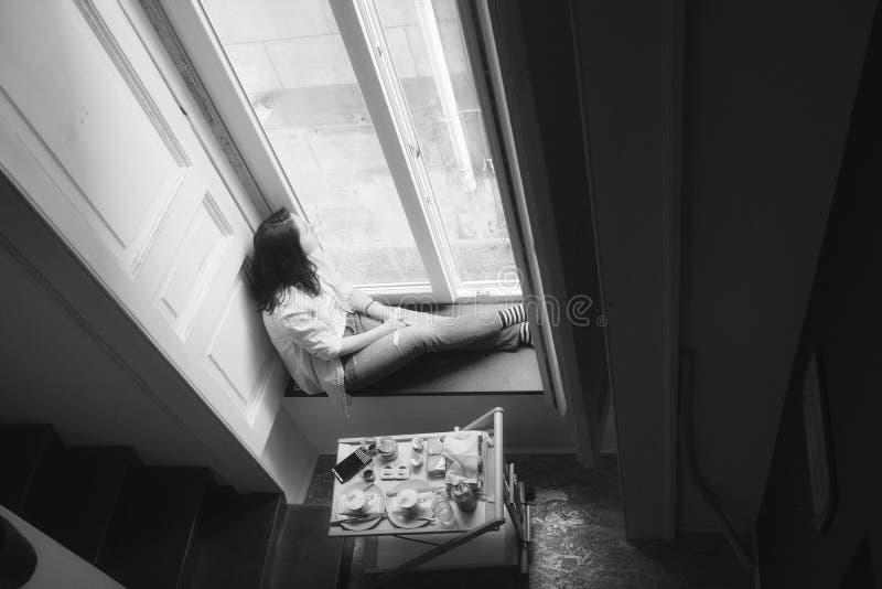 Esperando na janela, menina, preto e branco foto de stock