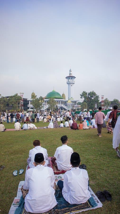 Esperando o sermão na frente da mesquita para a oração de Eid na cidade do alun-alun foto de stock