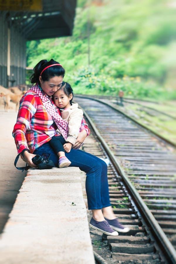 Esperando o trem Asiático com uma criança nas trilhas imagens de stock