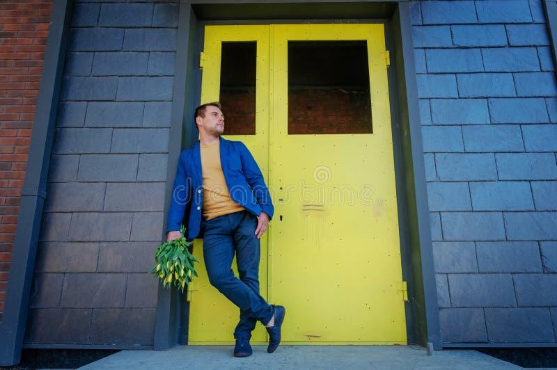 Esperando sua amiga Close-up do homem novo considerável no ramalhete esperto da terra arrendada do revestimento das flores imagem de stock