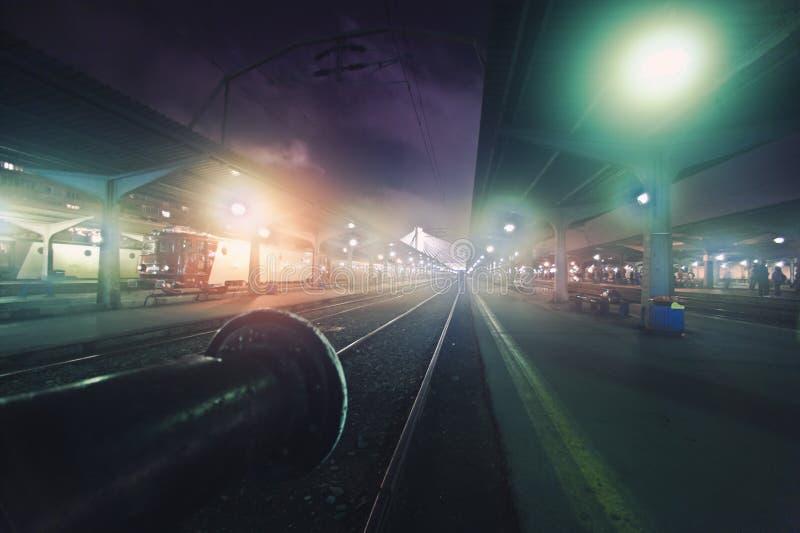 Esperar el tren en la noche fotos de archivo