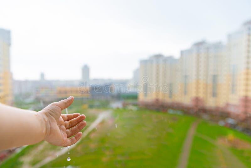 Esperas del niño para la lluvia en casa Lluvia del verano Tiempo Ni?ez en la ciudad foto de archivo