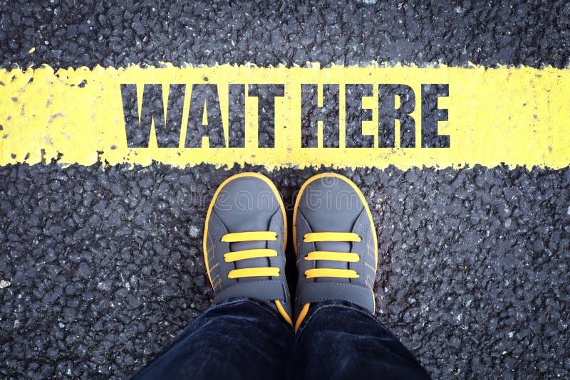 Espere aquí los pies detrás de la línea que espera foto de archivo libre de regalías