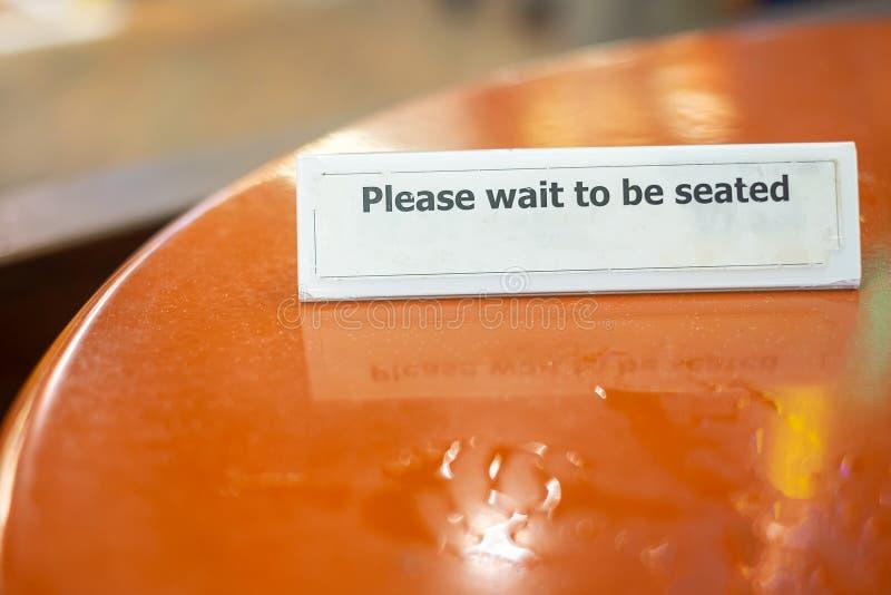 Espere por favor ao sinal assentado no tampo da mesa no restaurante imagens de stock royalty free