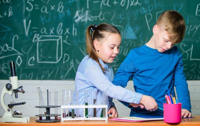 Esperimento astuto della scuola di comportamento degli studenti del ragazzo e della ragazza Analisi chimica Chimica occupata di s fotografia stock libera da diritti
