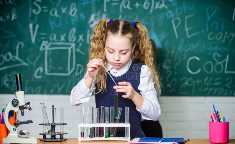 Esperimento astuto della scuola di comportamento dello studente della ragazza Liquidi chimici di studio dell'allievo della scuola fotografia stock