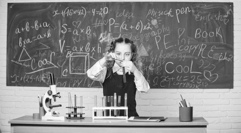 Esperimento astuto della scuola di comportamento dello studente della ragazza Liquidi chimici di studio dell'allievo della scuola fotografie stock libere da diritti