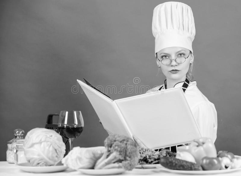 Esperto culinario Cuoco unico della donna che cucina alimento sano La ragazza ha letto ricette culinarie superiori del libro le l fotografia stock libera da diritti