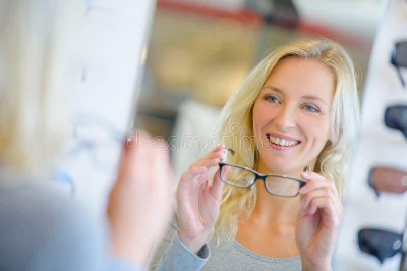 Espetáculos de tentativa de sorriso do cliente fêmea do retrato na loja ótica imagens de stock