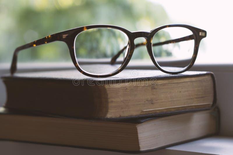 Espetáculos do vintage em livros ao lado de uma janela fotos de stock