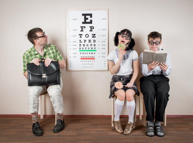 Espetáculos vestindo de três pessoas em um escritório no doutor fotos de stock