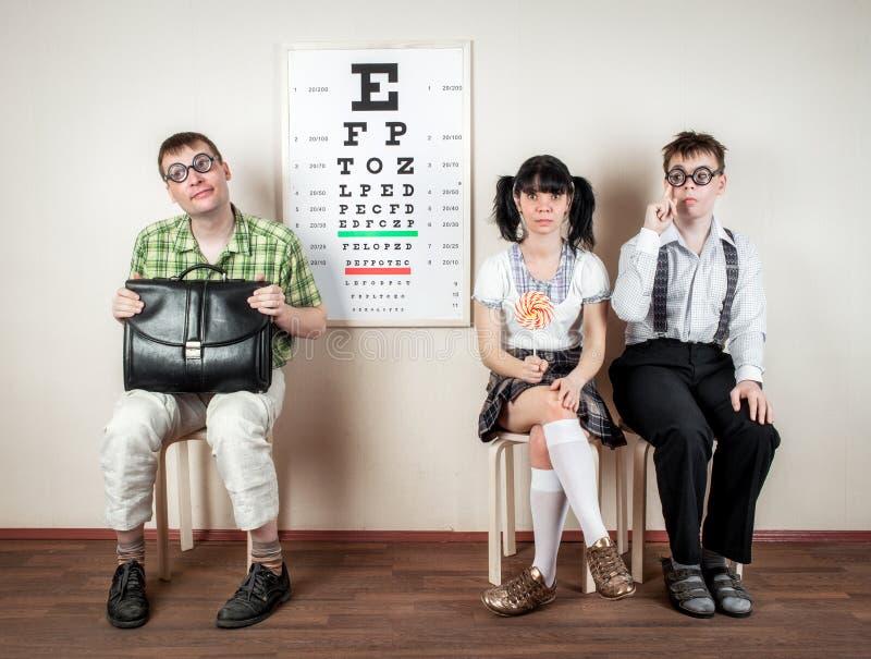 Espetáculos vestindo de três pessoas em um escritório no doutor imagem de stock royalty free