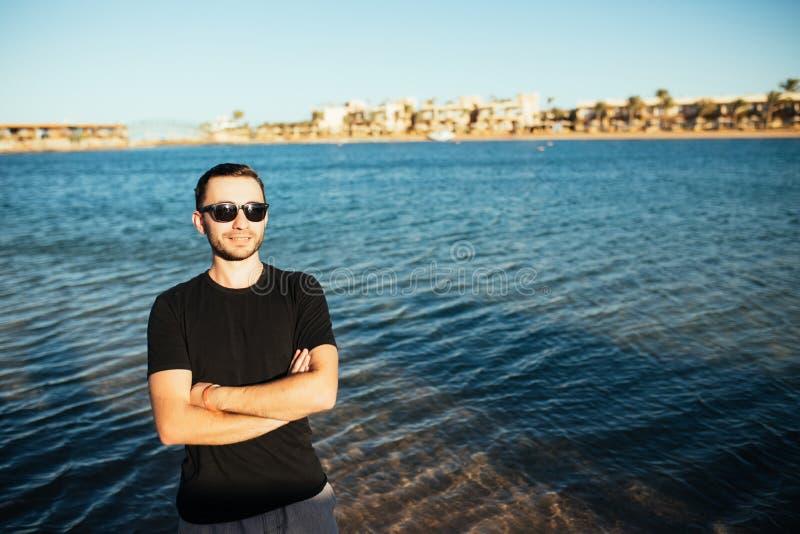 Espetáculos vestindo do homem considerável novo e divertimento ter na praia do mar fotos de stock royalty free