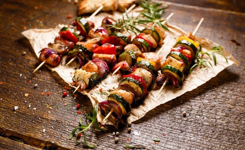 Espetos da carne e de vegetais grelhados em uma tabela de madeira imagens de stock royalty free
