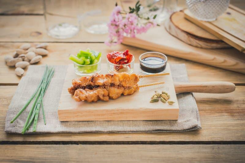 Espetos da galinha com molho e pimentas vermelhas e verdes foto de stock