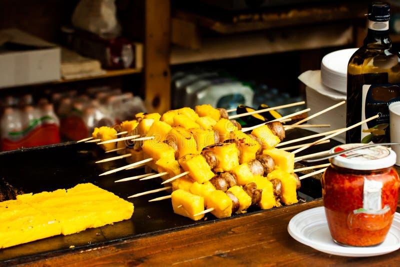 Espetos deliciosos do polenta e da salsicha cozinhados na grade em um restaurante do fast food imagens de stock