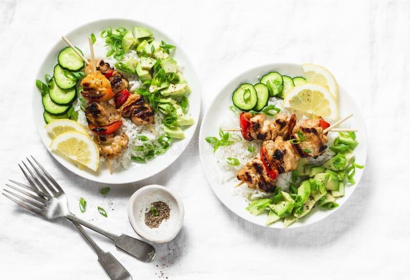 Espetos grelhados da galinha do cal do mel do pimentão com salsa do arroz e do abacate no fundo claro, vista superior imagens de stock
