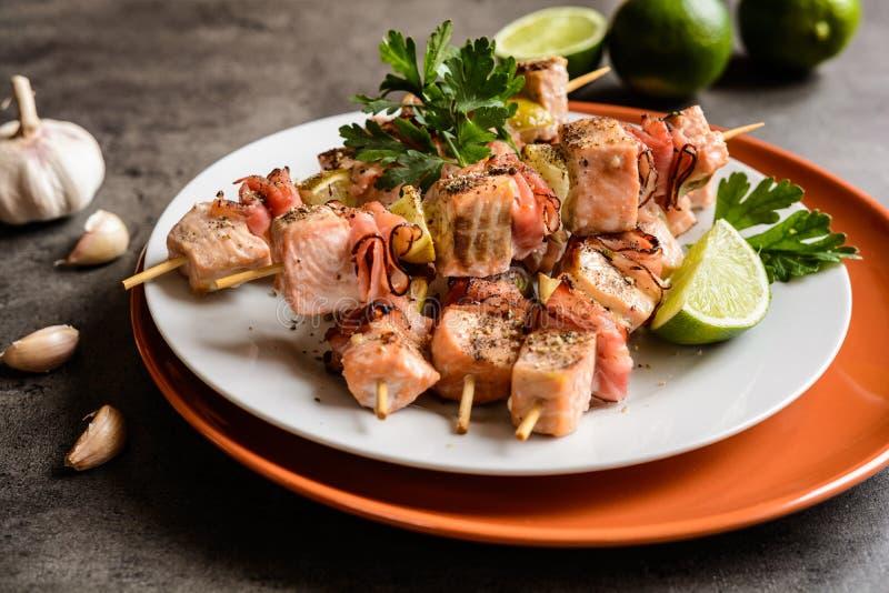 Espetos salmon Roasted com bacon e cal imagens de stock royalty free