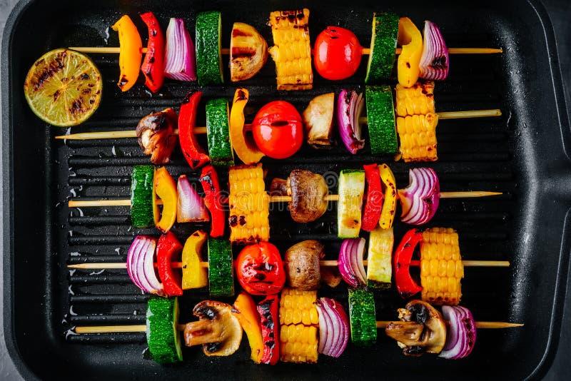 Espetos vegetais grelhados com milho doce, paprika, abobrinha, cebola em uma bandeja da grade fotos de stock