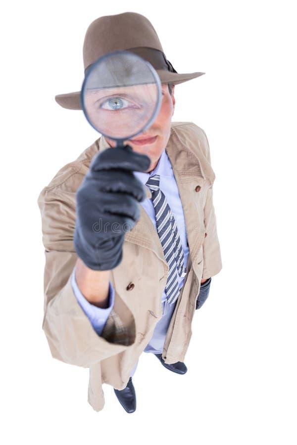 Espião que olha através da lente de aumento foto de stock