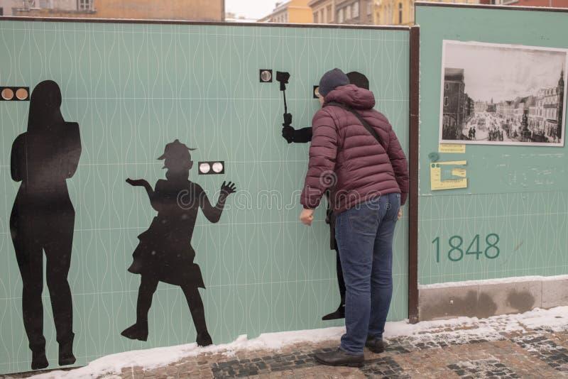 Espiar através de um furo em uma cerca de madeira moderna com espaço para afixar a informação imagem de stock