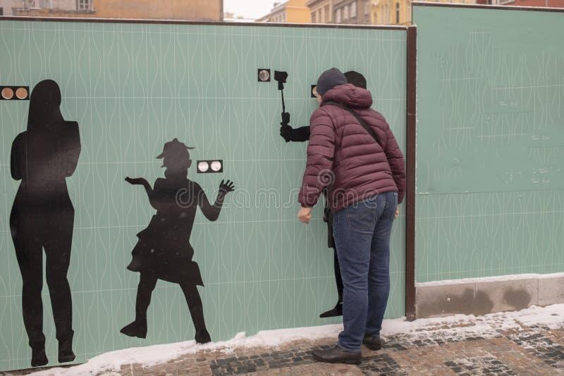 Espiar através de um furo em uma cerca de madeira moderna com espaço para afixar a informação imagens de stock