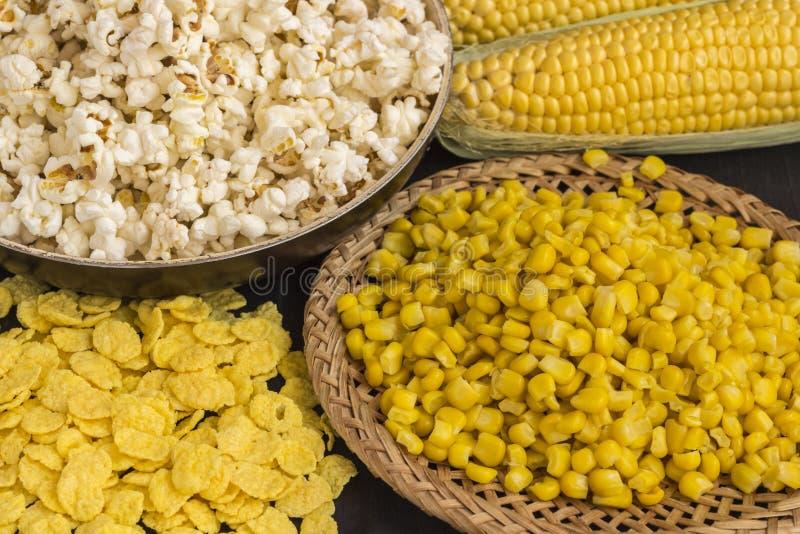 Espiga de milho crua, grões do milho em uma placa de vime, pipoca e flocos foto de stock