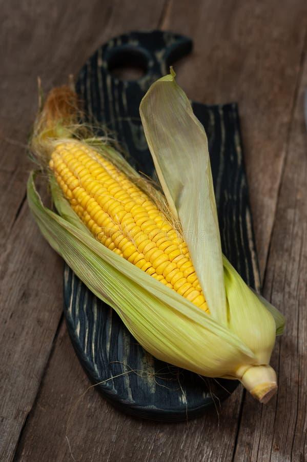 Espiga de milho crua na placa de corte de madeira fotografia de stock