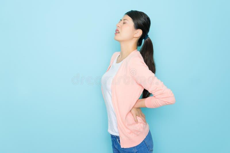 Espina dorsal bonita joven de la sensación del ama de casa dolorosa imagenes de archivo