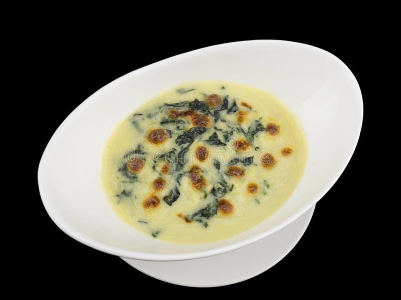 Espinaca cocida con el queso aislado en el fondo negro con imagen de archivo libre de regalías