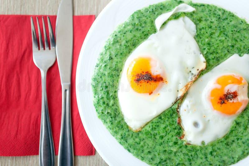 Espinafres com os ovos picantes no café da manhã fotografia de stock