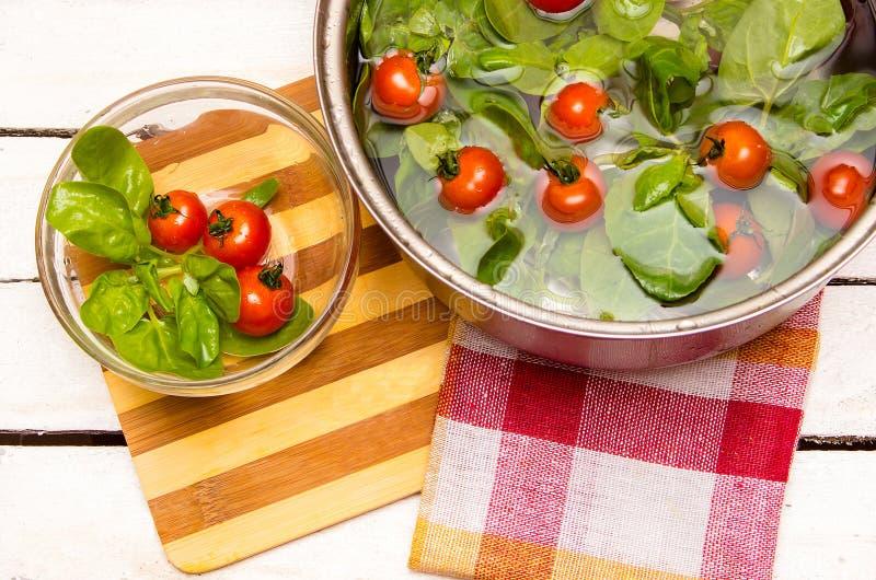Espinafres frescos, tomates de cereja em uma caçarola com água foto de stock royalty free