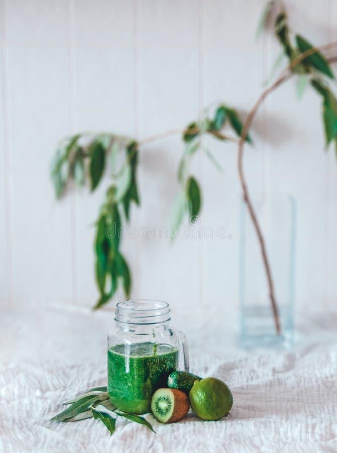 Espinafres verdes do batido da desintoxicação Frutos e grama brilhantes de quivi do cal do pepino da cor Matéria têxtil branca fo foto de stock