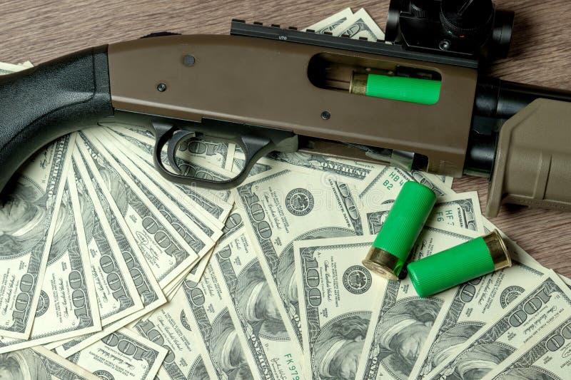 Espingarda e cartuchos em dólares Conceito para o crime, comércio de braços global, venda das armas Caça ilegal, caçando foto de stock royalty free