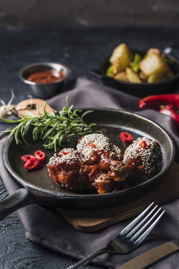 Espinillas asadas a la parrilla del pollo en salsa de tomate con pimienta de chile en una cacerola oscura y patatas cocidas en un fotos de archivo libres de regalías