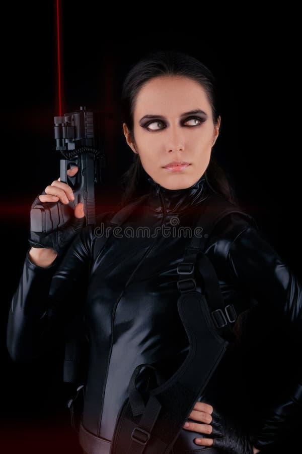 Espion de femme tenant l'arme à feu avec des vues de laser image libre de droits