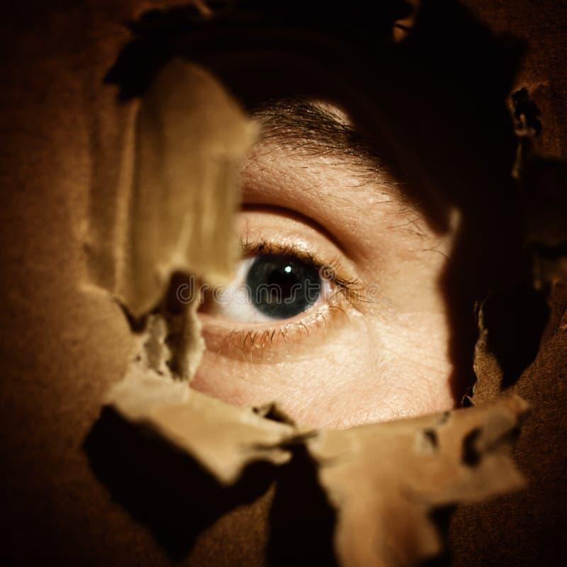 Espionnage masculin de yeux images stock