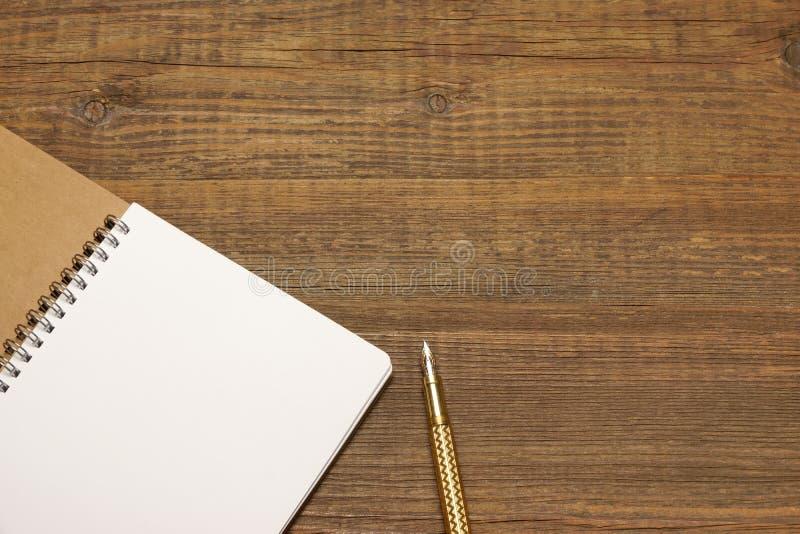Espiral aberta - caderno encadernado com white pages e pena do ouro fotografia de stock