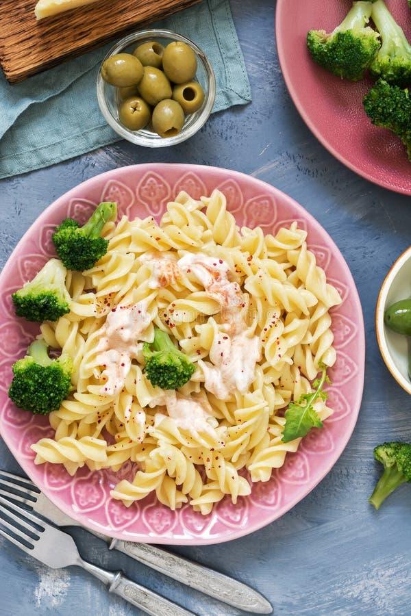 Espiral da massa com brócolis no fundo cinzento, vista superior Conceito italiano do alimento imagem de stock